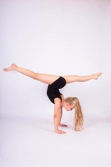 Uma jovem ginasta faz uma fenda invertida com as mãos em uma parede branca isolada.