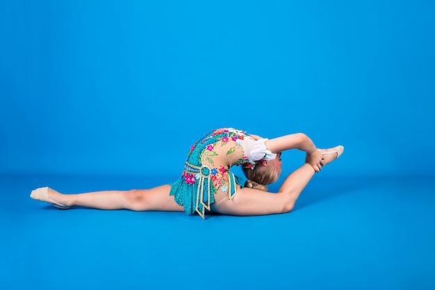 Uma jovem ginasta realiza um exercício com uma deflexão nas costas em uma parede azul isolada