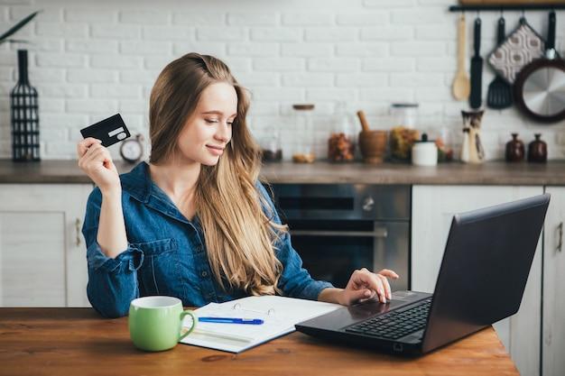 Uma jovem grávida bonita trabalha em casa em modo de auto-isolamento em quarentena e faz compras online