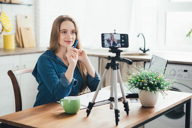 Uma jovem grávida bonita trabalha em casa em modo de auto-isolamento em quarentena e grava vídeos em seu smartphone