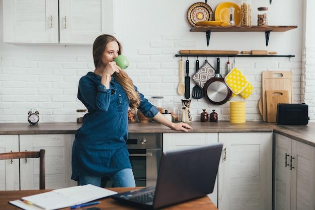 Uma jovem grávida bonita trabalha em casa em modo de isolamento em quarentena e faz uma pausa para descansar com um café