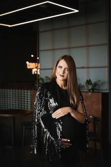 Uma jovem grávida com maquiagem brilhante em um vestido preto da moda e uma jaqueta brilhante na moda.