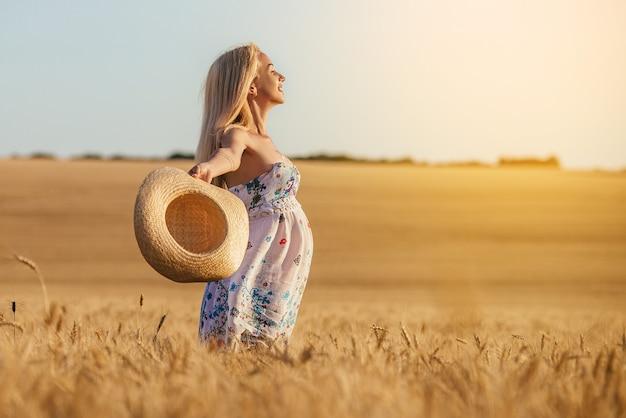 Uma jovem grávida em um campo de trigo