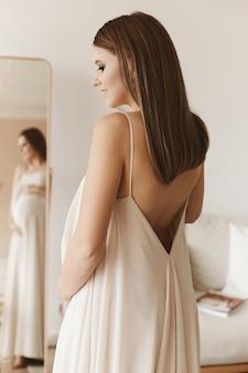Uma jovem grávida linda em um vestido longo e moderno está em frente ao espelho segurando h.