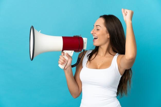 Uma jovem hispânica em um fundo azul isolado gritando em um megafone para anunciar algo em posição lateral