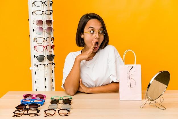 Uma jovem hispânica experimentando óculos está contando uma notícia secreta sobre a travagem e olhando para o lado