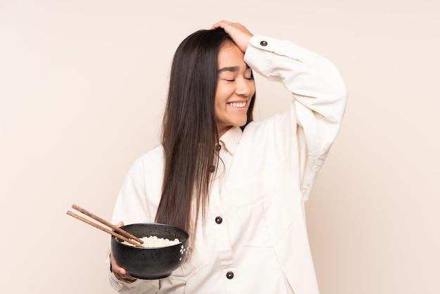 Uma jovem indiana isolada em um bege percebeu algo e pretendia a solução enquanto segurava uma tigela de macarrão com pauzinhos