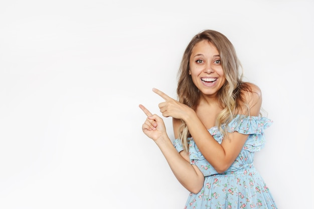 Uma jovem indica uma cópia do espaço vazio para o texto ou desenho com dois dedos apresentando o produto