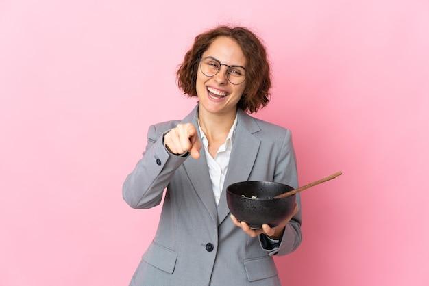 Uma jovem inglesa isolada na parede rosa aponta o dedo para você com uma expressão confiante, segurando uma tigela de macarrão com pauzinhos
