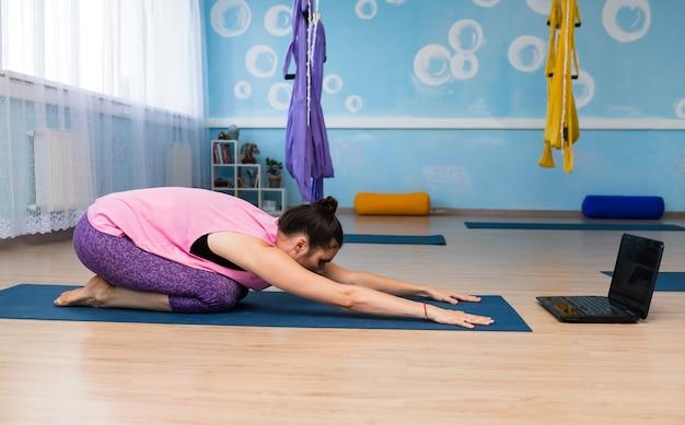 Uma jovem instrutora realiza um treino online em uma sala de ginástica