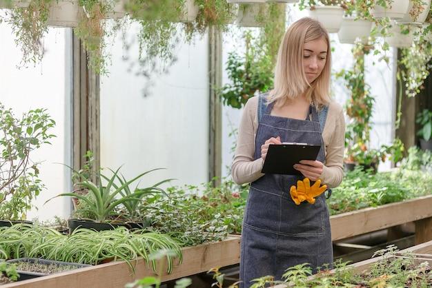 Uma jovem jardineira mantém um registro das flores em uma estufa na primavera.