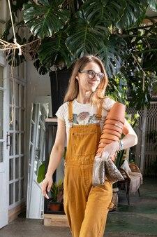 Uma jovem jardineira na estufa carrega vasos e pedras para replantar o jardim doméstico para a loja de flores