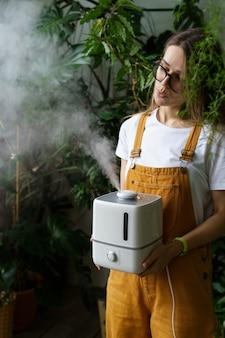 Uma jovem jardineira usa umidificador para umidade em ambientes fechados durante a estação de aquecimento, cuidando de plantas domésticas