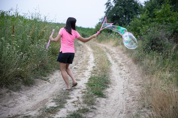 Uma jovem lança enormes bolhas de sabão na bela natureza de fundo, vista traseira.
