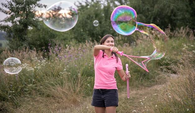 Uma jovem lança grandes bolhas de sabão coloridas entre a grama da natureza.
