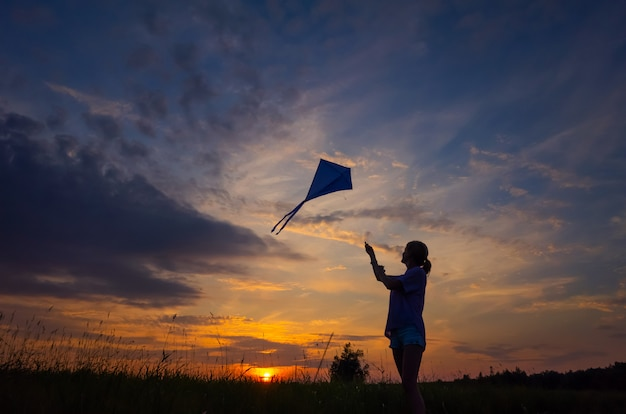 Uma jovem lança uma pipa no céu. silhueta contra o pôr do sol