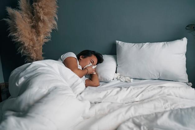 Uma jovem latina assoando o nariz com um lenço de papel enquanto está na cama