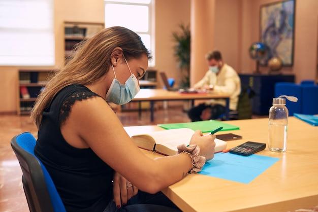 Uma jovem latina com máscara estudando na biblioteca da universidade
