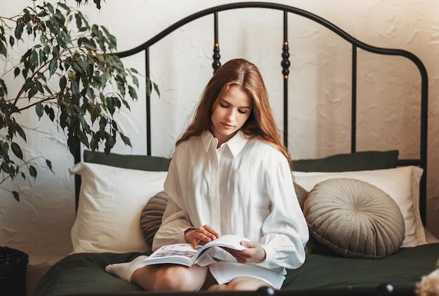 Uma jovem linda com cabelo comprido e uma camisa branca se senta na cama e lê um livro
