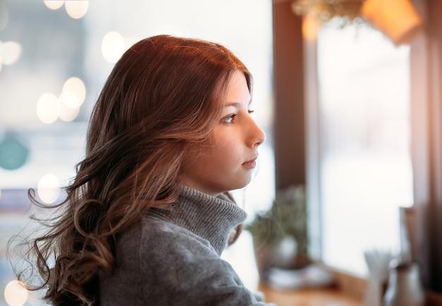 Uma jovem linda com cabelo comprido se senta a uma mesa em um café e olha pela janela