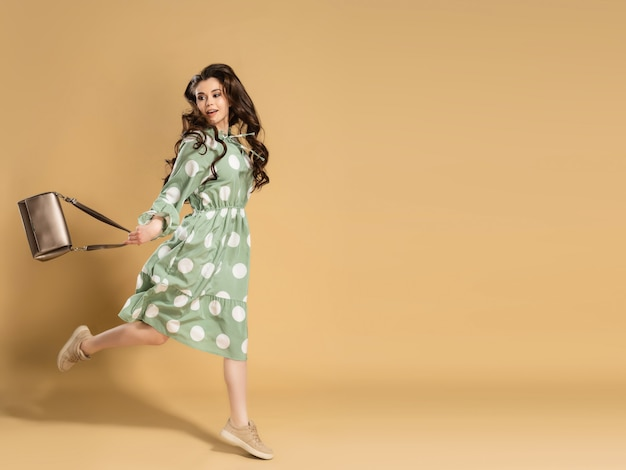 Uma jovem linda com cabelo longo cacheado em um vestido com bolinhas está pulando com uma bolsa nas mãos em uma laranja.
