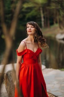 Uma jovem linda com longos cabelos castanhos, em um longo vestido vermelho com um anel ao redor do lago.