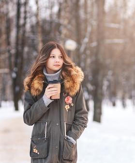 Uma jovem linda com um copo de papel de café caminhando no parque
