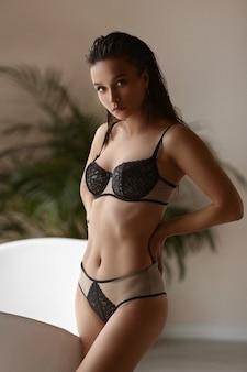 Uma jovem linda com um corpo perfeito em lingerie bege posando no banheiro