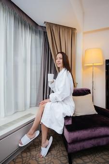 Uma jovem linda com um jaleco branco bebe café em seu quarto de hotel