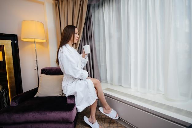 Uma jovem linda com um jaleco branco bebe café em seu quarto de hotel.