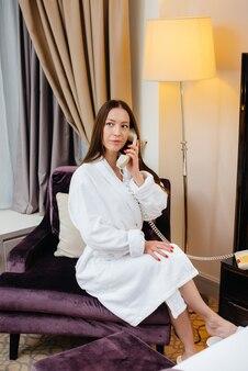 Uma jovem linda com um jaleco branco está falando ao telefone em seu quarto de hotel.