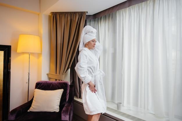 Uma jovem linda com um jaleco branco está perto da janela em seu quarto de hotel.