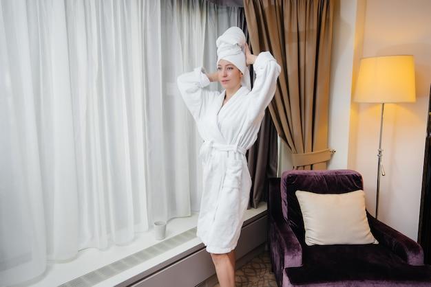 Uma jovem linda com um jaleco branco está perto da janela em seu quarto de hotel