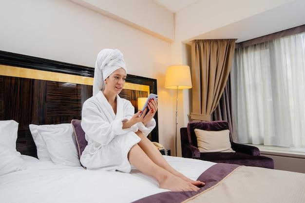 Uma jovem linda com um jaleco branco tira uma selfie em seu telefone em seu quarto de hotel.