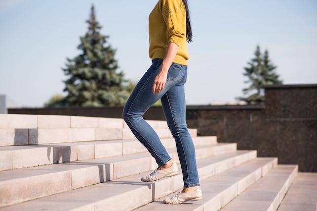 Uma jovem, linda e atraente menina morena caucasiana com um suéter amarelo subindo as escadas.