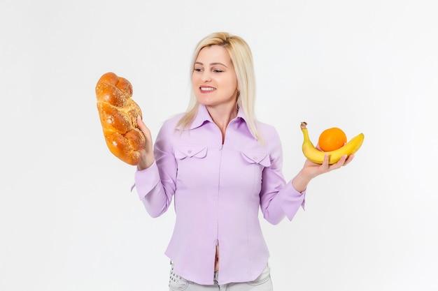 Uma jovem linda e feliz com cabelo comprido segurando bananas na mão direita e um pão na mão esquerda, isolado sobre fundo branco