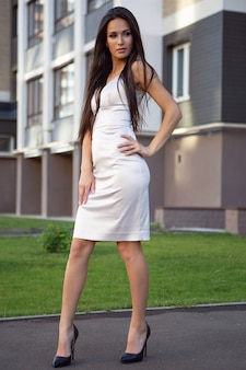 Uma jovem linda em um lindo vestido está caminhando por uma rua da cidade