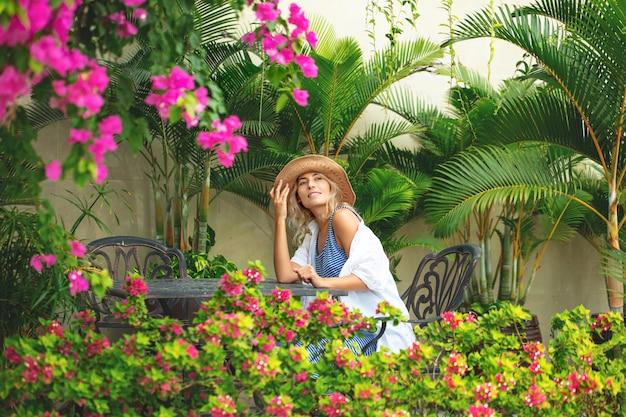 Uma jovem linda está sentada em um restaurante rodeado por um jardim tropical