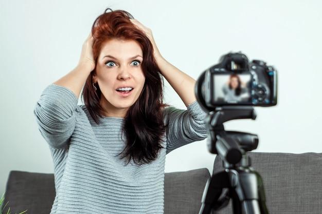 Uma jovem linda está sentado na frente de uma dslr e gravando um vlog