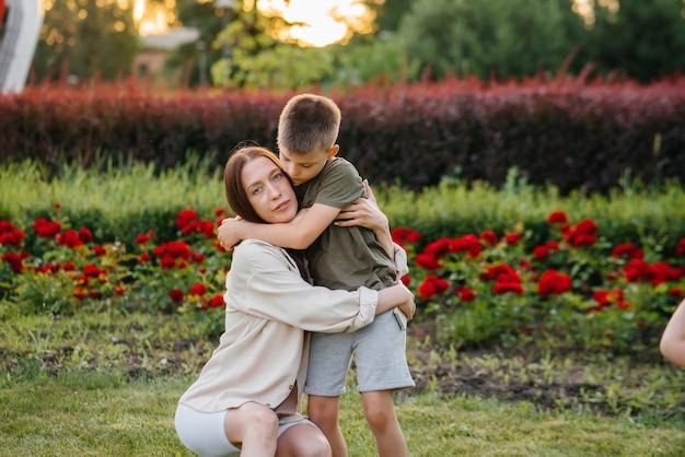 Uma jovem linda mãe beija e abraça o filho pequeno durante o pôr do sol no parque. família feliz passeio no parque.