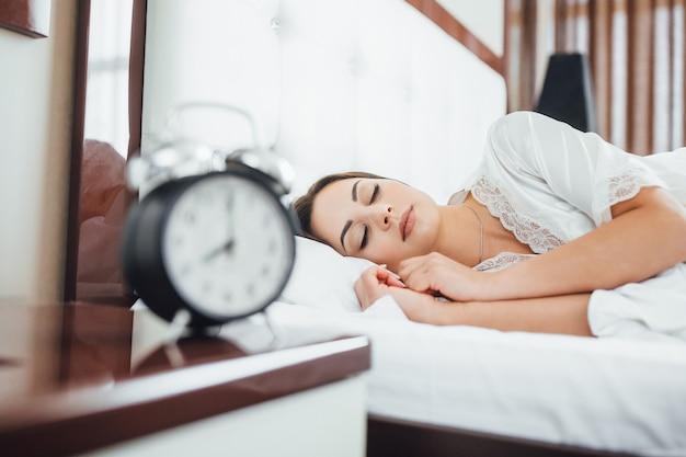 Uma jovem linda morena de manhã acorda na cama com um despertador preto.