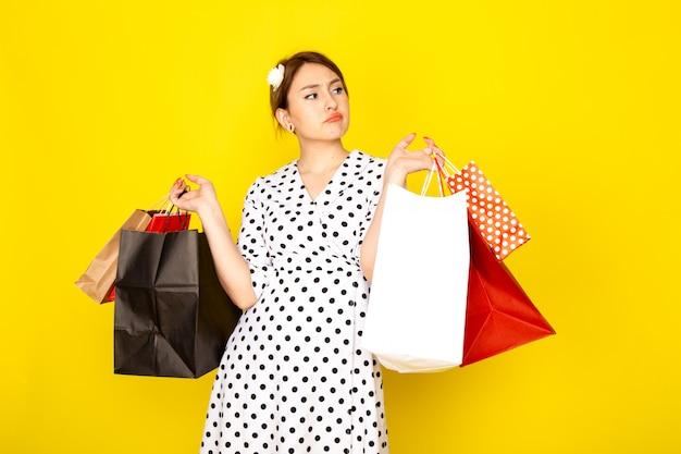 Uma jovem linda mulher de frente para um vestido de bolinhas preto e branco segurando pacotes de compras em amarelo