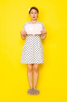Uma jovem linda mulher de frente para um vestido de bolinhas preto e branco segurando uma placa branca em amarelo