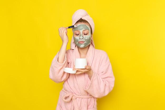 Uma jovem linda mulher de roupão rosa fazendo maquiagem