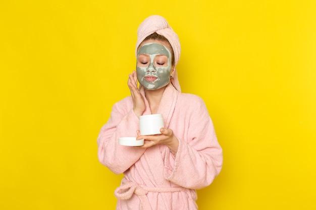Uma jovem linda mulher de roupão rosa segurando uma lata de creme e usando-a