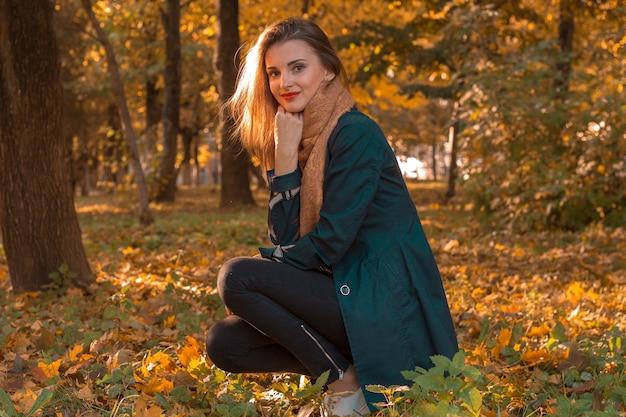 Uma jovem linda sentada nas folhas no outono park e mantém uma mão perto do rosto