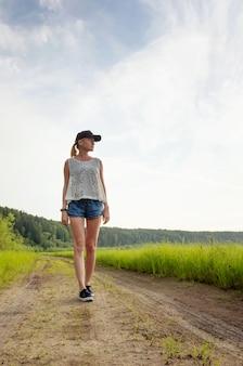 Uma jovem loira caucasiana em shorts, uma t-shirt e um boné caminha ao longo de um caminho no meio do campo e parece longe.