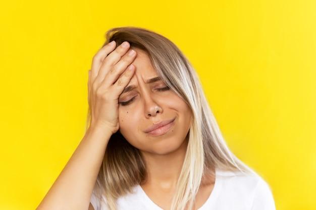 Uma jovem loira com dor de cabeça, segurando a testa isolada em um fundo de cor amarela