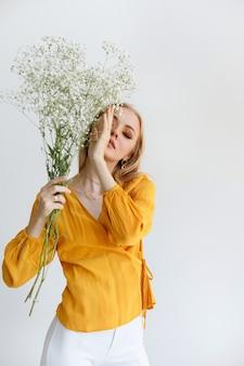 Uma jovem loira com flores secas cobre o rosto com a mão. maquiagem da moda