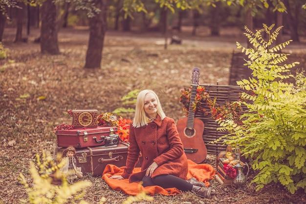Uma jovem loira de aparência europeia com um casaco laranja de outono está sentada em uma manta com um sorriso no rosto